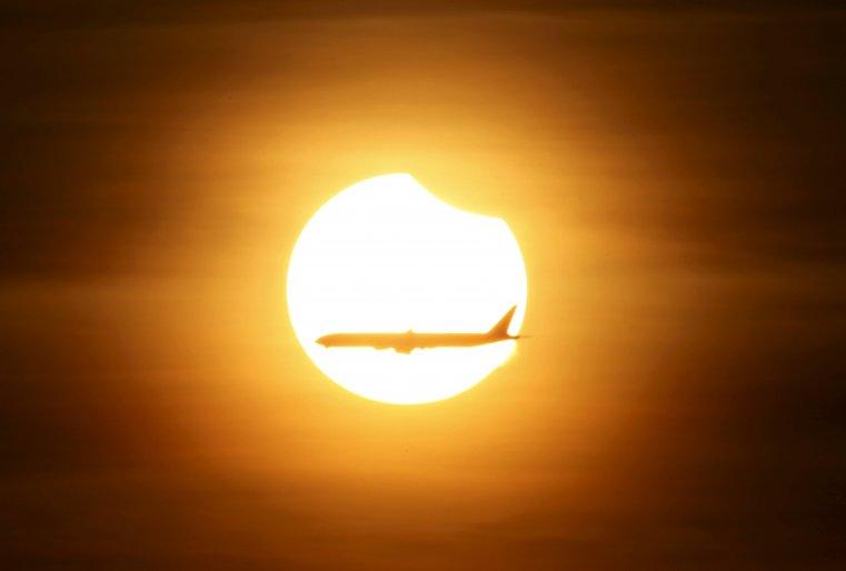 Самолет летит на фоне солнца в тот момент, когда наступает частичное солнечное затмение. Сингапур. © REUTERS