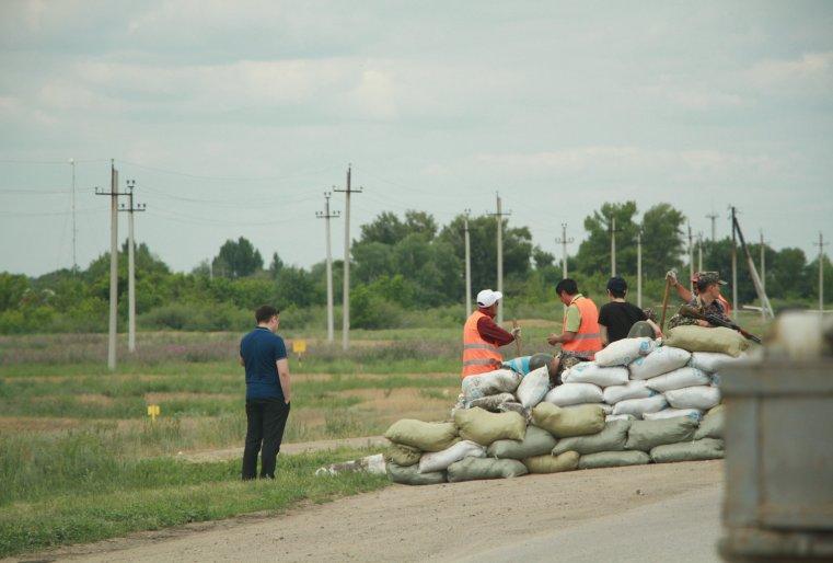 Рабочие возводят укрепление для полицейских из мешков с песком на выезде из Актобе
