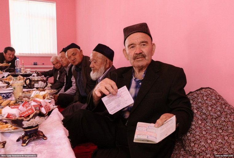 Гость из Узбекистана показывает свой паспорт и миграционную карту.