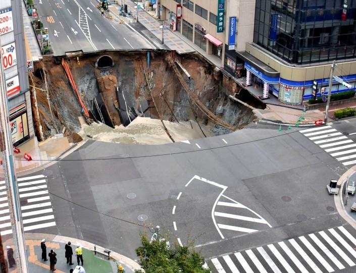 Японские рабочие закапывают 30-метровую яму вцентре города