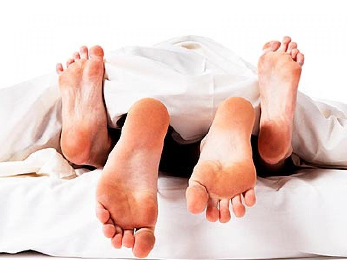 una foto di un uomo e una donna a letto, si vedono solo i piedi in primo piano