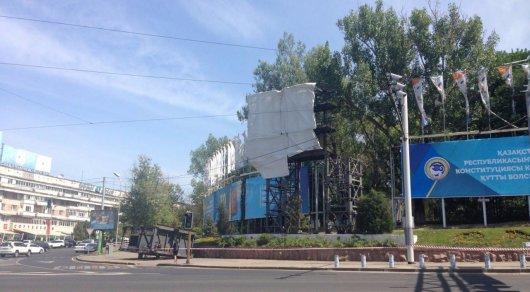 Рабочие демонтируют большой дисплей на площади Республики в Алматы